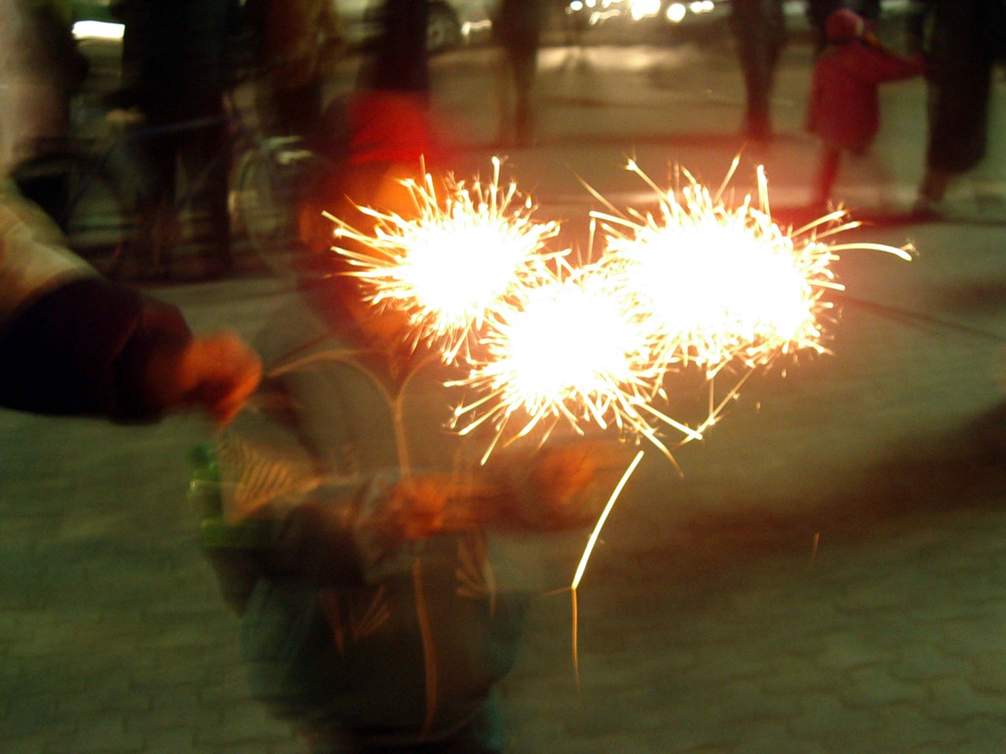 Xiao Yang's son Julian holds three sparklers at the Lantern Festival in the Railway District's main square.