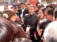 """The voice of the people! Fang Di, also known as, """"The Radio Man"""", interviews angry demonstrators outside of a Korla department store. They'd all just lost their jobs because of some sort of swindle."""