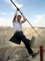 William shows off his physique by hanging over Tiemenguan on a steel cable.
