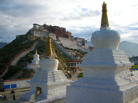 The Potala Palace at sunrise, with three white stupas in the foreground.