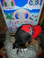A young thangka painter in Lhasa wearing a Che Guevara baseball cap.