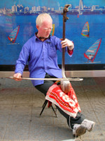 It's not often that you see an albino Chinese man, much less one playing an erhu under the hot sun.