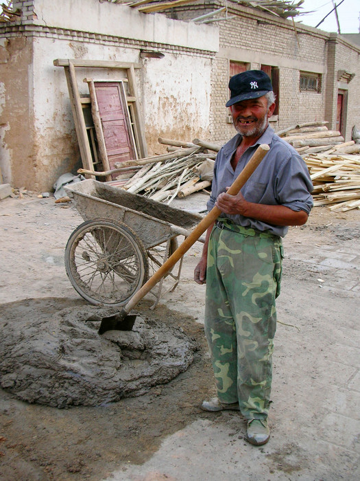 The world's most unlikely Yankee's fan stirs cement in Kuqa's old city.