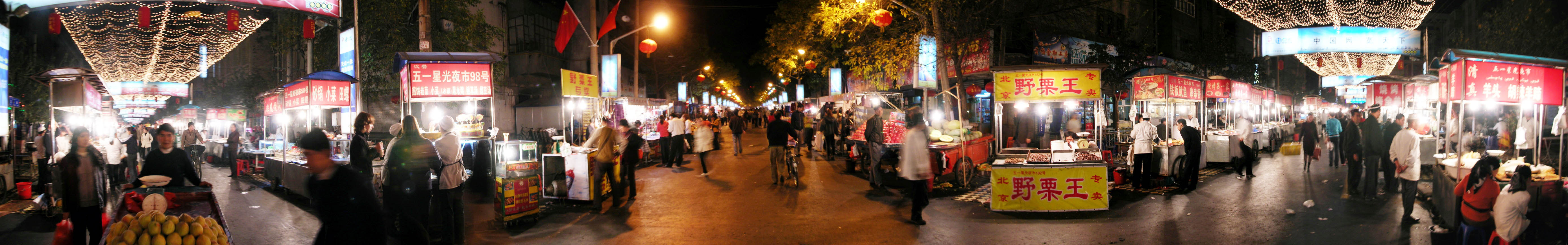 A 180-degree panorama shot of a night market in Urumqi.