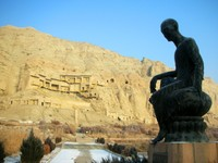 The Kizil Thousand Buddha Caves from afar, with a statue of the guy who founded the caves' monastery in the foreground. (I forget his name, and my guidebook is not at my side.)