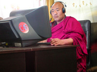 A monk video-conferencing with a friend in one of Xiahe's suprisingly high-quality Internet cafes.