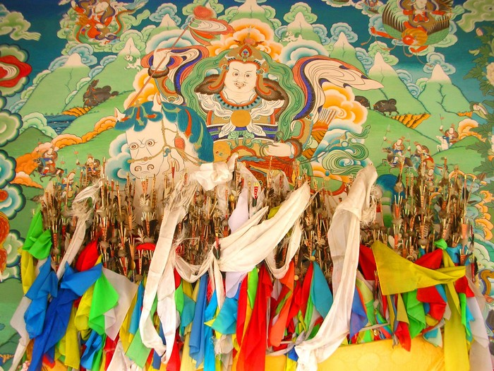 Beautiful wall painting behind a display of arrows and prayer flags.