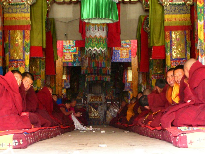 A long row of monks sitting inside Labrang's main temple.
