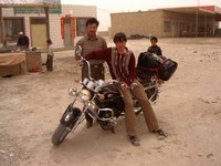 The last small town before the Taklamakan. I stopped to eat a nan bread while these Uyghurs checked out my motorcycle.