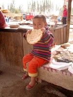 I stopped on the way to Hotan (Hetian) to grab a snack, and snapped this photo of a little Uyghur girl enjoying a nan bread.