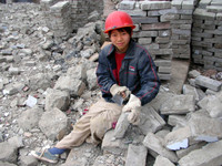 A young construction worker, helping to disassemble old Fengdu's buildings brick-by-brick.