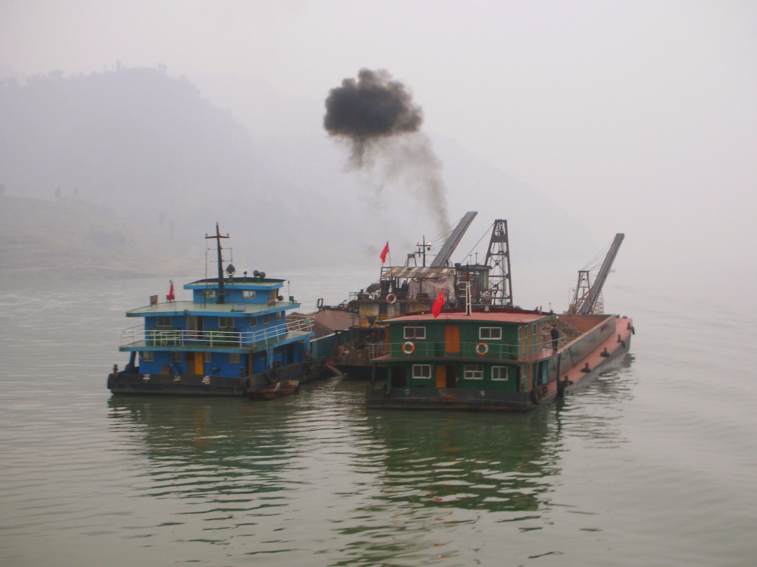 A couple of industrial looking boats float down the Yangzi.