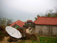 Stopping at a village along the Minor Three Gorges. The homemade satellite dish improves their reception of mindless CCTV programming.
