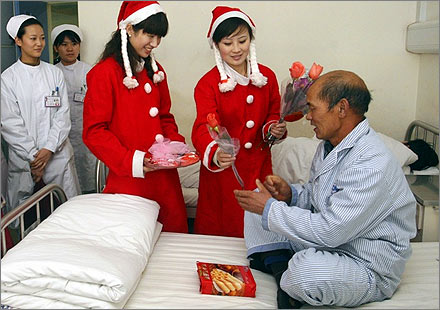 Nurses dressed as Santa Claus present flowers and gifts to a patient at a hospital in Xi'an, Shaanxi province December 24, 2007. REUTERS/Ben Ruan