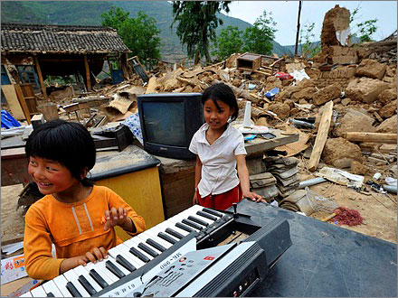 A girl plays on a damaged electronic organ at the site of the collapsed Douping Primary School in Kangxian, Gansu province May 21, 2008.