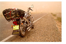 Motorcycle in a sandstorm. Taklimakan Desert, Xinjiang, China. May 2005.