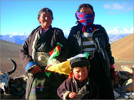 Three members of a Tibetan family pose for tourist yuan.