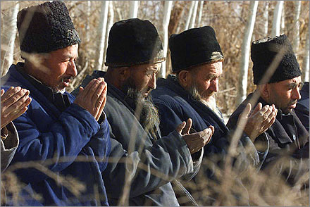 Uyghur men praying outdoors.