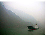 A ship passes through the rising waters of the Three Gorges along the Yangzi River, January 2006.